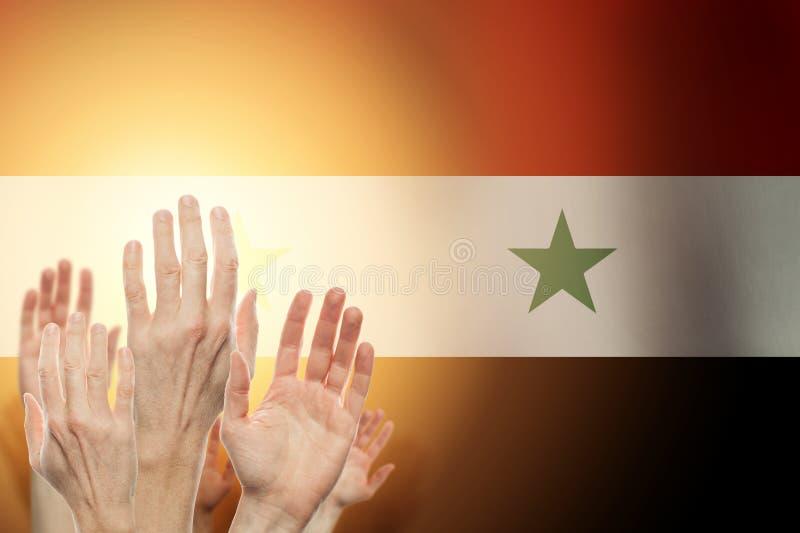 Gente que aumenta las manos y la bandera Siria en fondo Concepto patri?tico foto de archivo libre de regalías