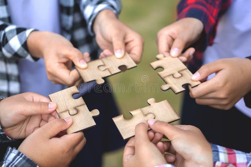 Gente que ayuda en el rompecabezas de junta, cooperaci?n en la toma de decisi?n, ayuda del equipo en solucionar problemas y traba foto de archivo libre de regalías
