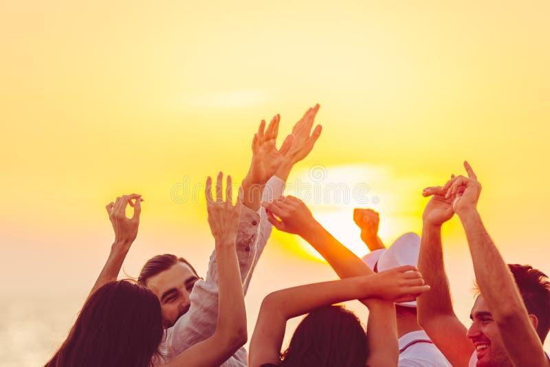Gente que baila en la playa con las manos para arriba concepto sobre partido, música y gente imagen de archivo