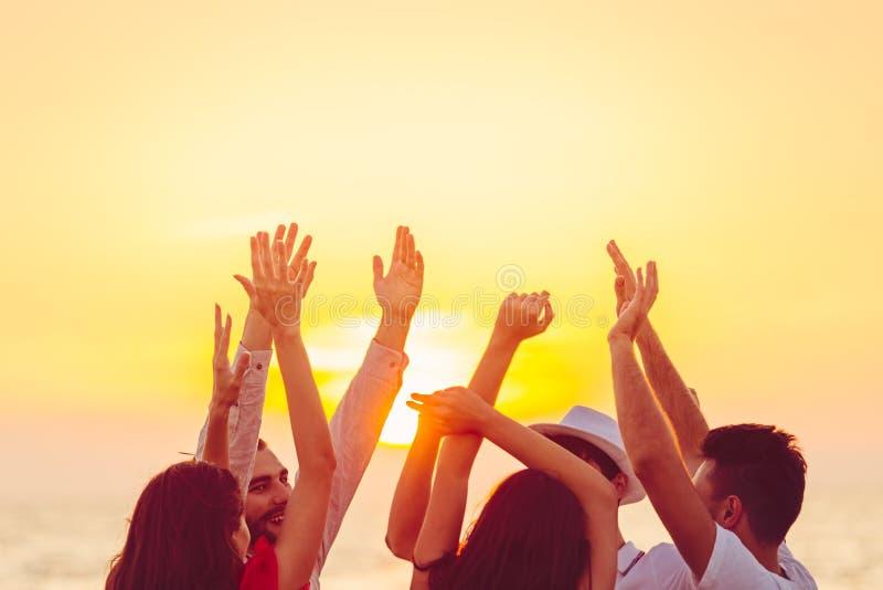 Gente que baila en la playa con las manos para arriba concepto sobre partido, música y gente foto de archivo libre de regalías
