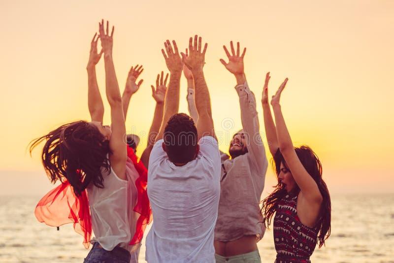 Gente que baila en la playa con las manos para arriba concepto sobre partido, música y gente foto de archivo