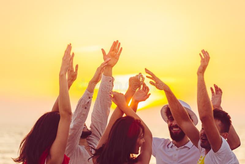 Gente que baila en la playa con las manos para arriba concepto sobre partido, música y gente imagen de archivo libre de regalías