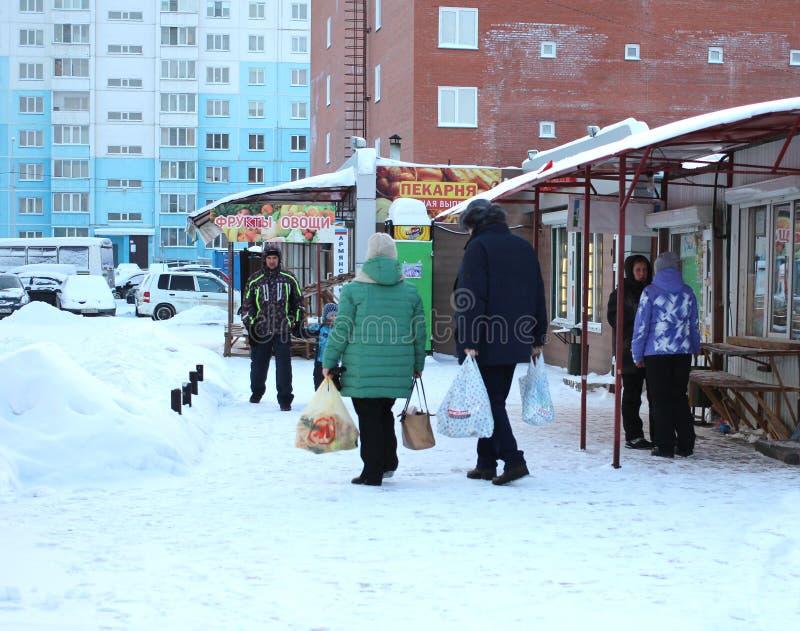 Gente que camina abajo de la calle más allá de la tienda en el invierno fotos de archivo