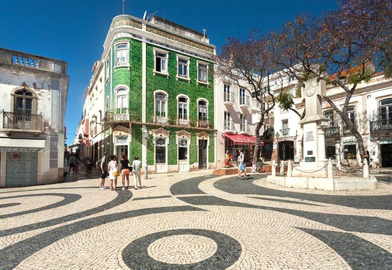 Gente que camina alrededor de casas históricas con las paredes de las baldosas cerámicas, en la calle soleada de la ciudad de Alg imagen de archivo