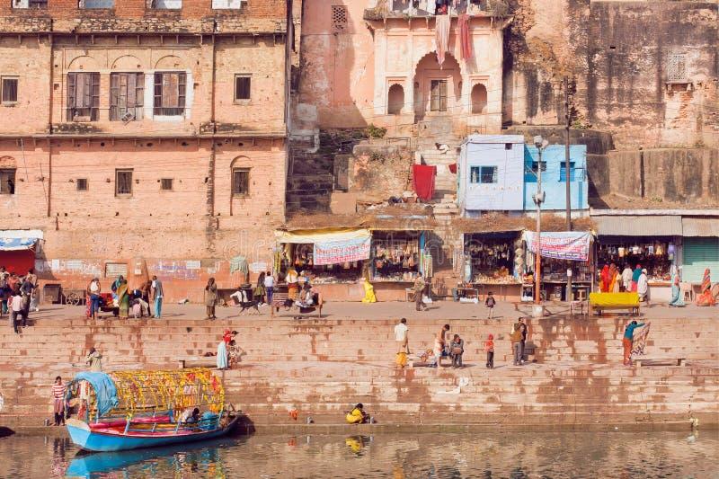 Gente que camina cerca de la orilla del río de la ciudad india vieja imagen de archivo