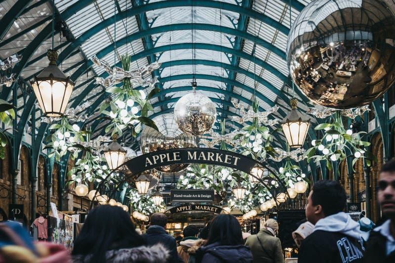 Gente que camina dentro del mercado adornado con las decoraciones de la Navidad, Londres, Reino Unido de Covent Garden fotografía de archivo