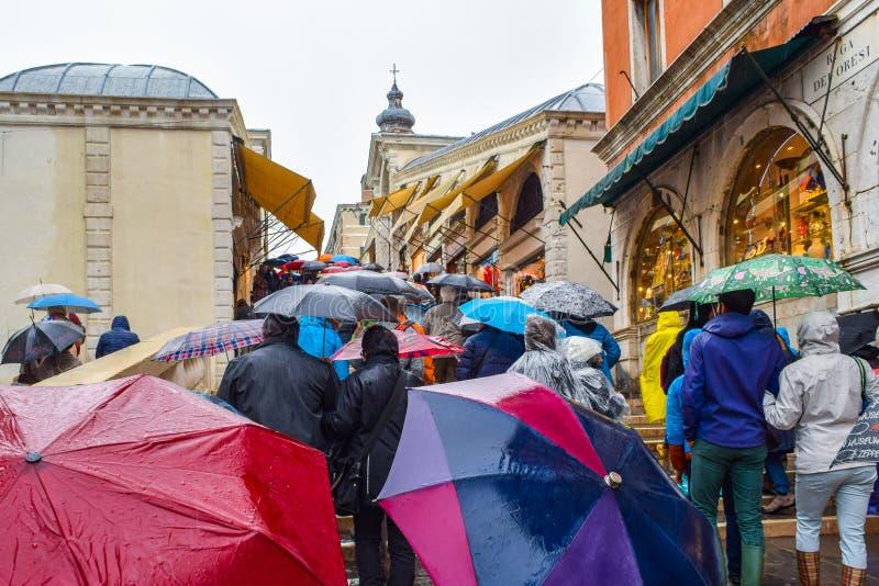 Gente que camina en día lluvioso con los paraguas en la escalera de Rialto Bridge Ponte de Rialto en Venecia, Italia foto de archivo