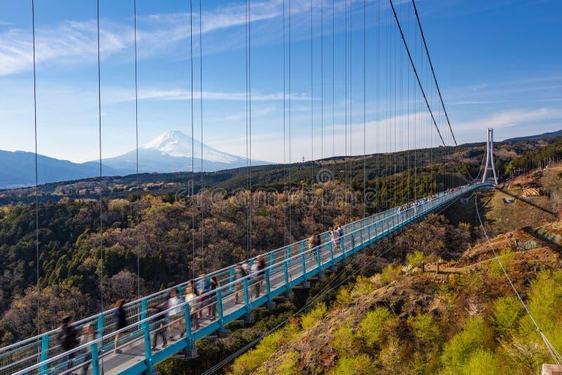 Gente que camina en el puente de Mishima Skywalk con el monte Fuji visto en el día distante, claro fotografía de archivo libre de regalías
