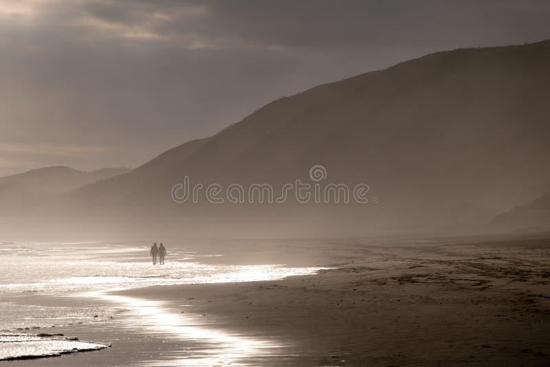 Gente que camina en la distancia lejana en la playa arenosa en Brenton en el mar, fotografiado en el ocaso Knysna, Sur?frica imagenes de archivo