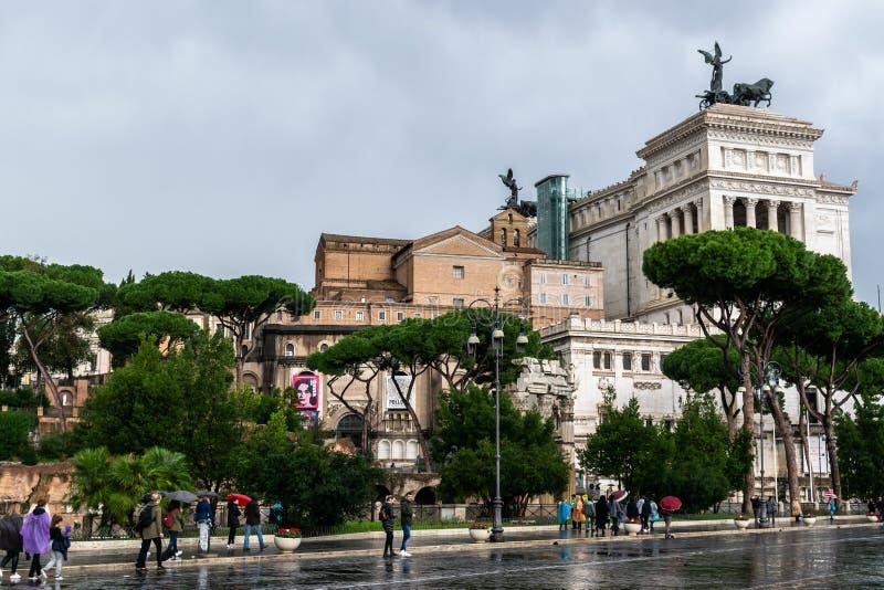 Gente que camina encendido vía la calle de Dei Fori Imperiali El monumento de Vittorio Emanuele II altera de la patria en fondo foto de archivo