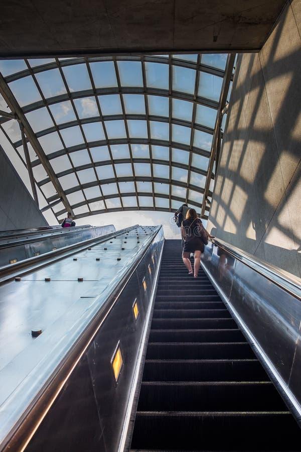 Gente que camina encima de la escalera móvil del subterráneo fotografía de archivo