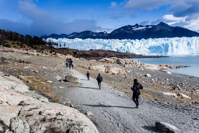 Gente que camina a lo largo de la trayectoria con Perito Moreno Glacier en el backg fotos de archivo libres de regalías