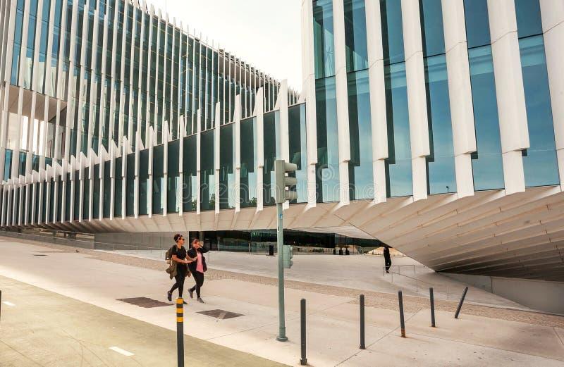 Gente que camina más allá de las paredes de cristal de las estructuras modernas de la arquitectura en la zona urbana de la ciudad imagenes de archivo