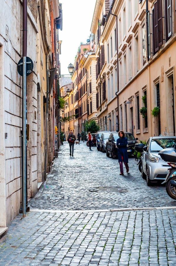 Gente que camina por la calle de piedra vieja medieval antigua de pavimentación de la ciudad en Roma, Italia foto de archivo