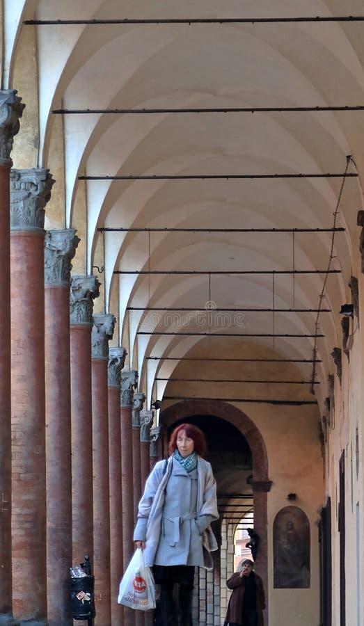 Gente que camina a través de un pórtico, calzada abrigada en Bolonia fotos de archivo