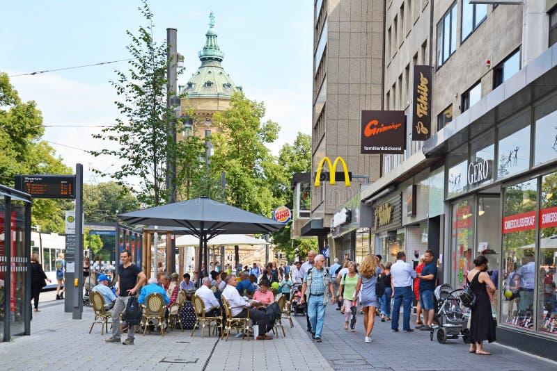 Gente que camina a través del centro de ciudad de Mannheim con las diversas tiendas y los cafés al aire libre en día de verano ca imágenes de archivo libres de regalías
