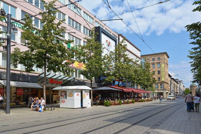 Gente que camina a través del centro de ciudad de Mannheim con las diversas tiendas y los cafés al aire libre en verano caliente imagenes de archivo