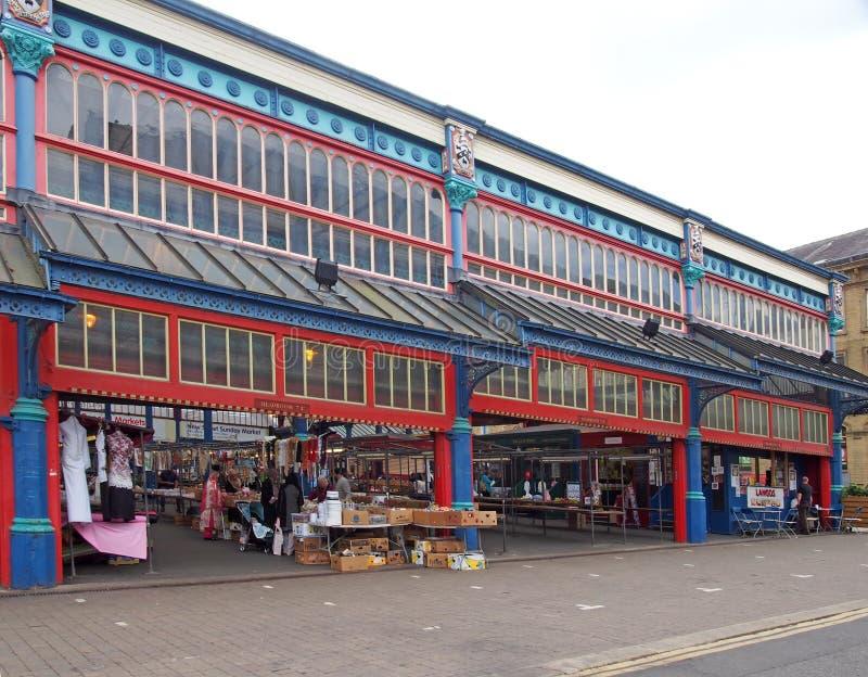 gente que camina y que hace compras en las paradas en el mercado de Huddersfield en West Yorkshire foto de archivo libre de regalías