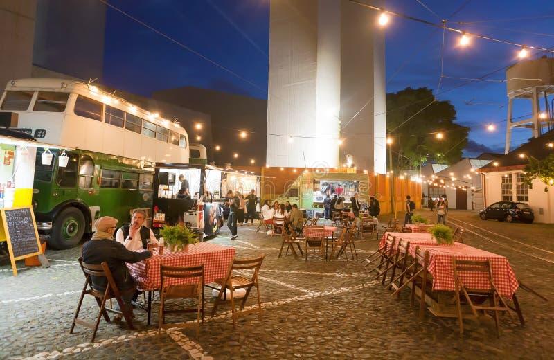 Gente que cena último en el restaurante al aire libre en zona urbana con las tablas y algunos camiones de los alimentos de prepar foto de archivo