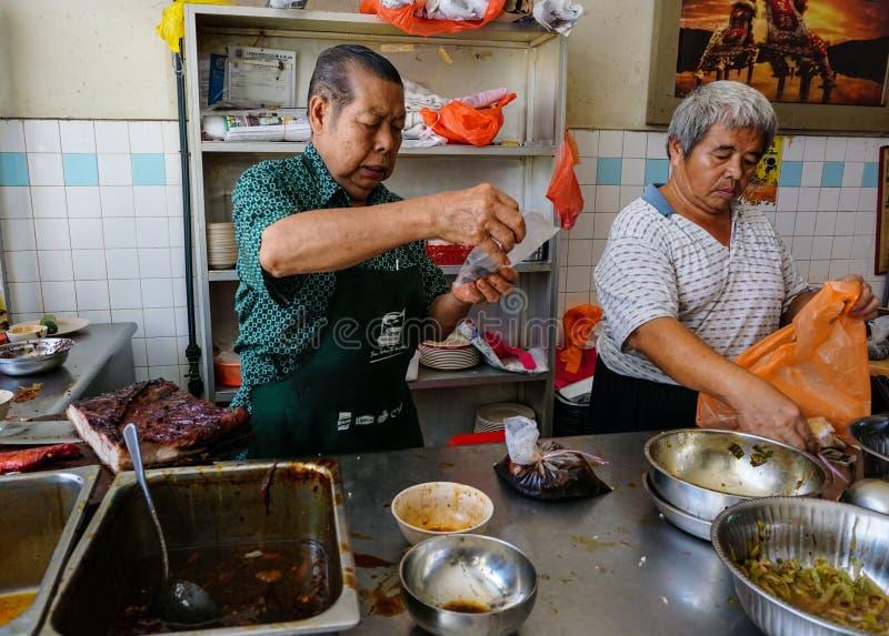 Gente que cocina en el restaurante en Melaka, Malasia fotos de archivo libres de regalías
