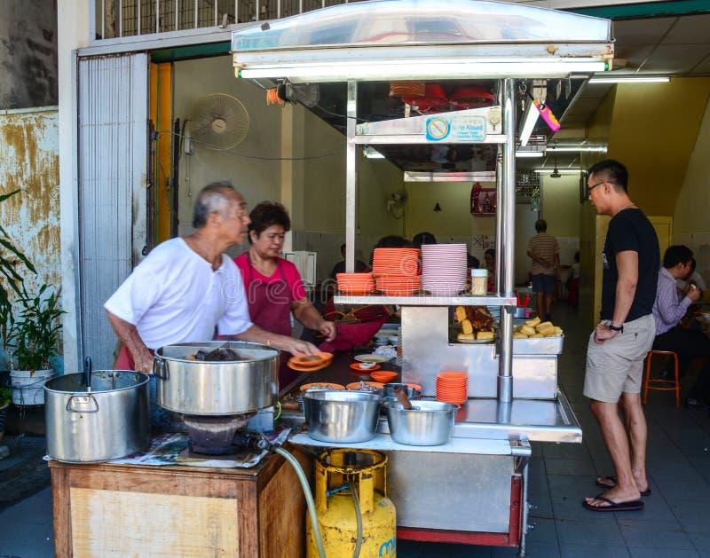 Gente que cocina las comidas chinas en el centro de la ciudad en Penang, Malasia imagen de archivo libre de regalías