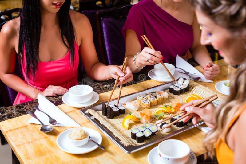 Gente que come el sushi en restaurante asiático fotografía de archivo