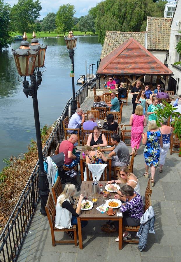 Gente que come hacia fuera por la orilla en la sol foto de archivo