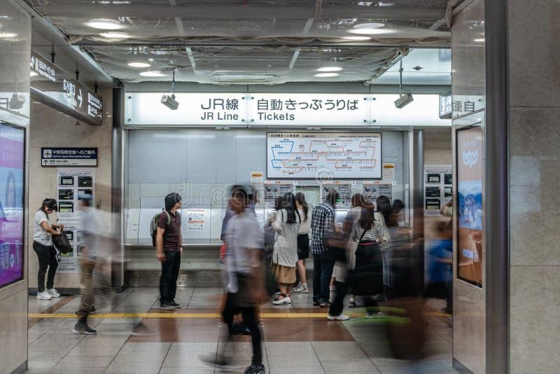 Gente que comprueba las rutas y que compra boletos de la máquina expendedora automatizada del boleto foto de archivo
