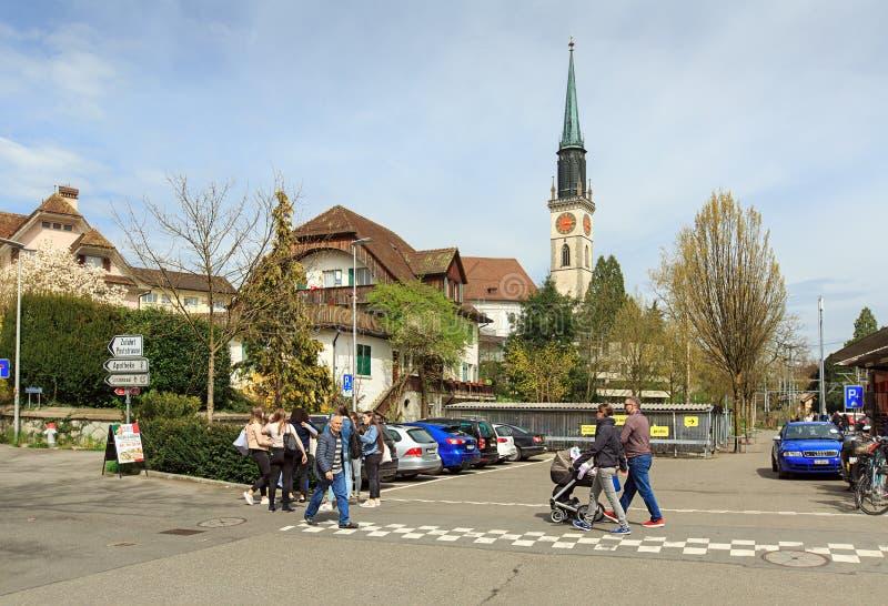 Gente que cruza el camino delante de la iglesia del santo Jacob Ciudad del Cham, cantón de Zug, Suiza imagenes de archivo
