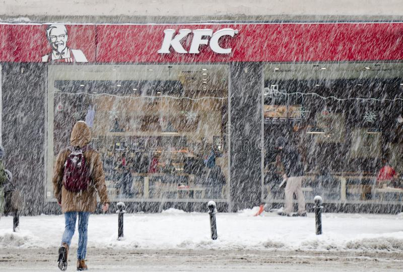 Gente que cruza la calle nevosa de la ciudad en nevadas pesadas hacia restaurante de los alimentos de preparación rápida de KFC fotos de archivo libres de regalías
