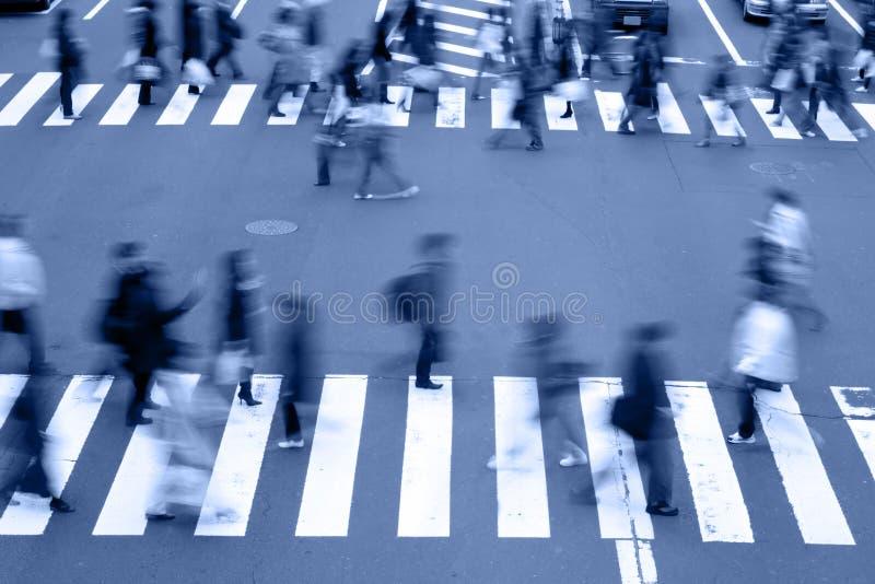 Gente que cruza los tonos calle-azules
