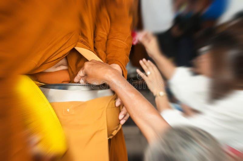 Gente que da las donaciones para el monje budista imagen de archivo