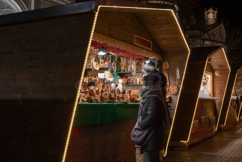 Gente que defiende delante de una cabina del mercado de la Navidad la noche, sur el Tyrol Italia de Meran imágenes de archivo libres de regalías