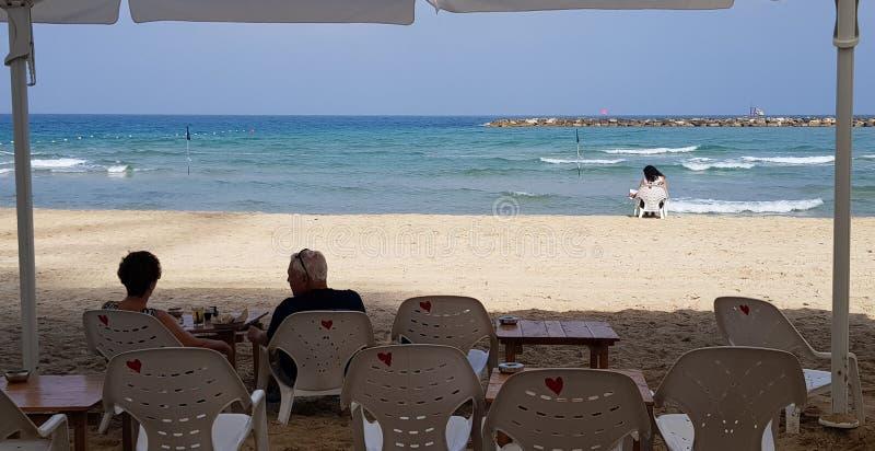 Gente que descansa sobre sillas plásticas en la playa fotografía de archivo libre de regalías