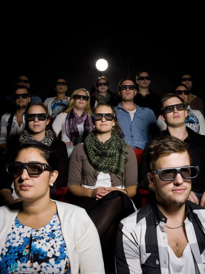 Gente que desgasta los vidrios 3d en el cine fotos de archivo