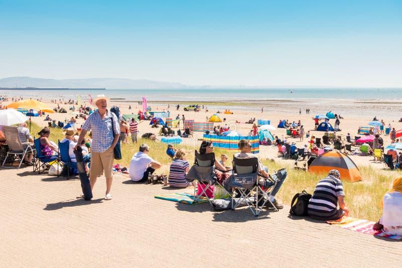 Gente que disfruta de día de verano caliente en la playa fotos de archivo