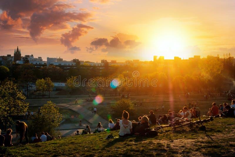 Gente que disfruta de la opinión sobre el cielo de la puesta del sol sobre horizonte del parque público Mauerpark el día de veran imagenes de archivo