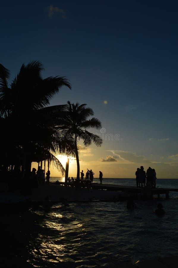 Gente que disfruta de una puesta del sol del Caribe, fractura, calafate de Caye, Belice imagenes de archivo