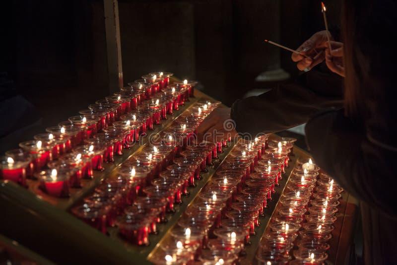 Gente que enciende velas en la catedral de Notre Dame en París, Francia La quema de una vela es una práctica usual en catolicismo fotografía de archivo