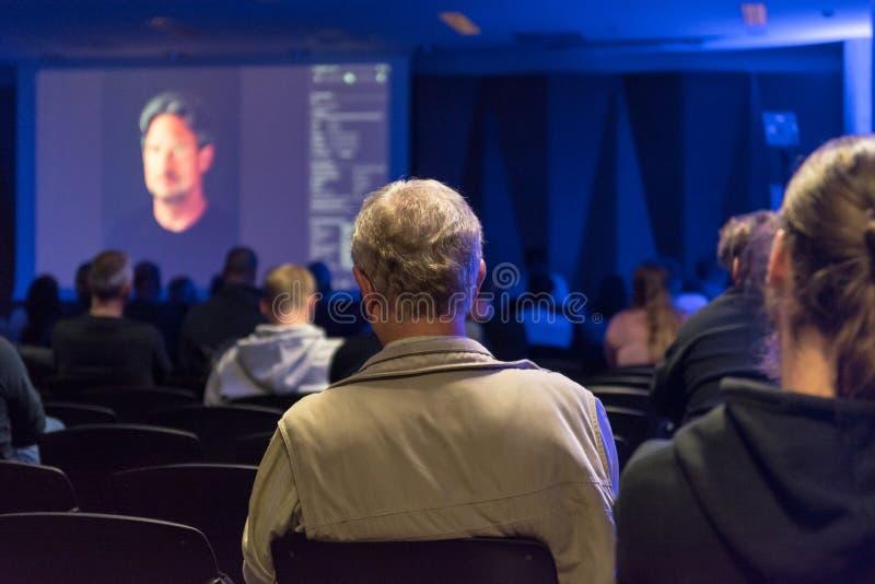 Gente que escucha la presentación en la conferencia interior foto de archivo libre de regalías