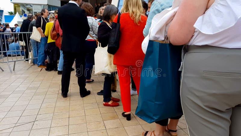Gente que espera en cola cerca de la entrada del festival de cine de Cannes, acontecimiento de la cinematografía foto de archivo