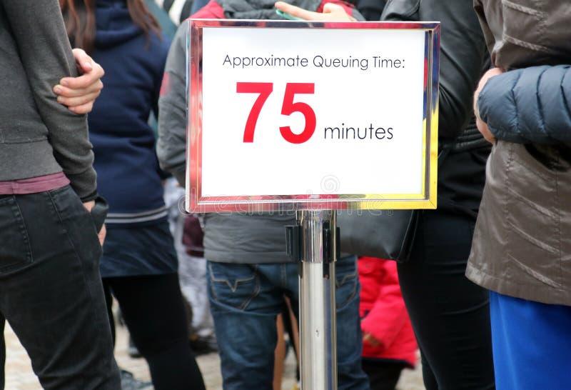 Gente que espera en una cola larga imagenes de archivo