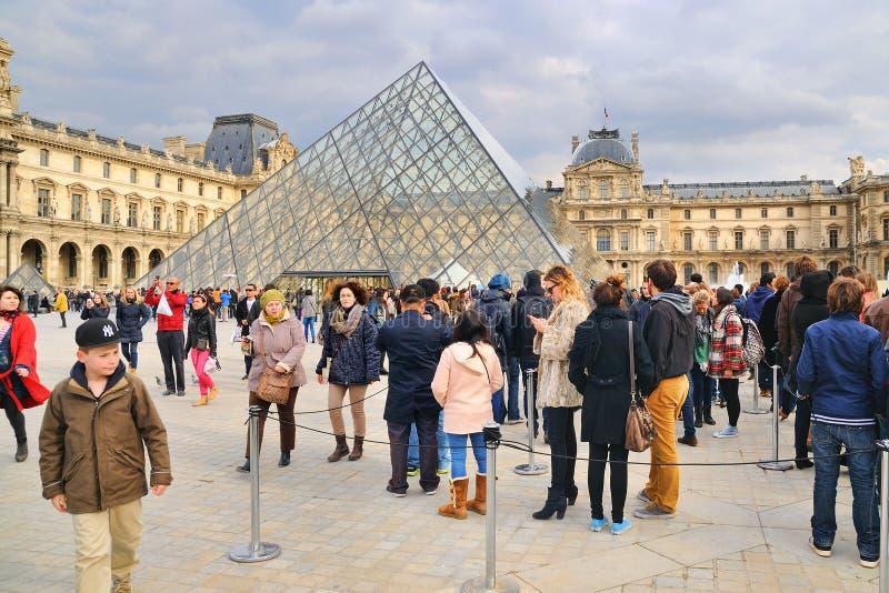 Gente que espera, usando una cola, para visitar el Louvre imagen de archivo libre de regalías