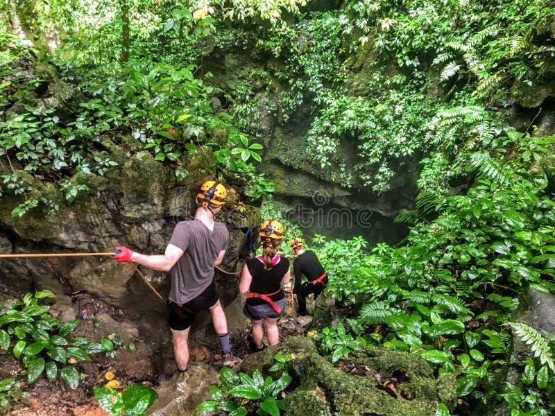 Gente que explora la selva mojada densa en Vietnam central al sistema de la cueva de Phong Nha foto de archivo