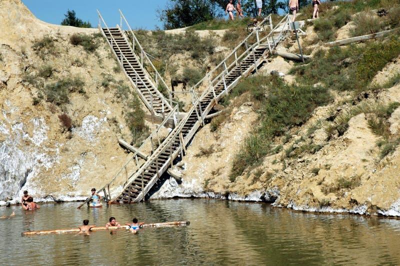 Gente que flota en el agua salada en una mina de sal abandonada foto de archivo