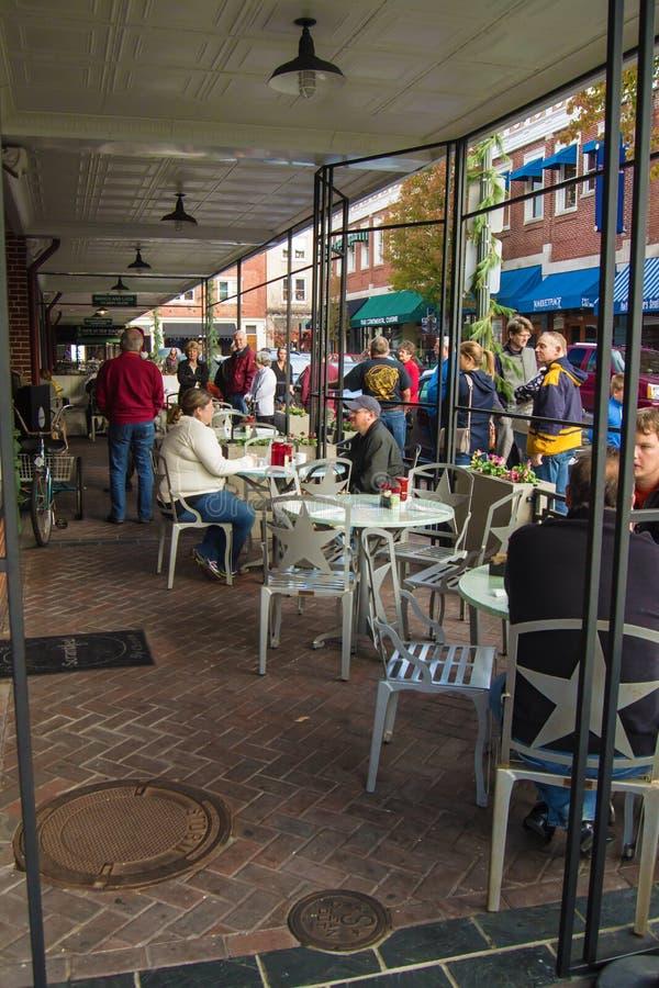 Gente que goza de un restaurante al aire libre de la calle foto de archivo