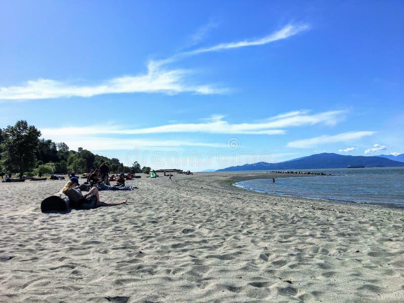 Gente que goza del sol en un día de verano hermoso a lo largo de las playas de los bancos españoles, en Vancouver, Columbia Britá imagen de archivo