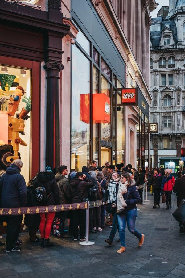 Gente que hace cola para conseguir dentro de tienda de LEGO en el cuadrado de Leicester, Londres, Reino Unido imágenes de archivo libres de regalías