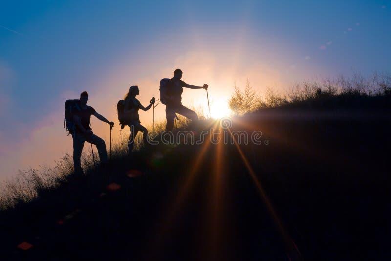 Gente que hace frente a salida del sol en una sesión de la formación de equipo imagen de archivo libre de regalías