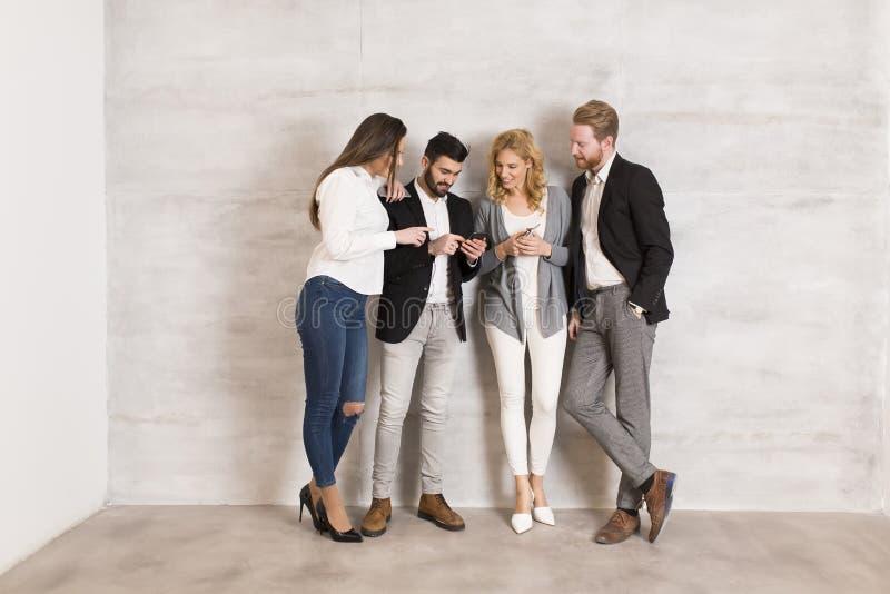 Gente que hace una pausa la pared con el teléfono móvil en manos imagen de archivo